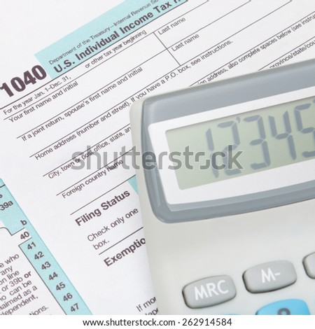 Calculator over US 1040 Tax Form - stock photo