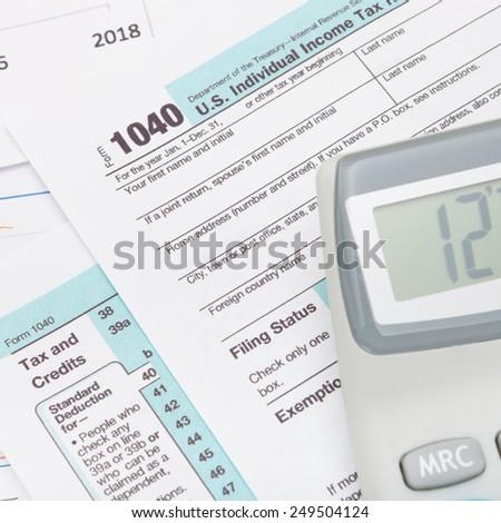 Calculator over US 1040 Tax Form - studio shot - stock photo