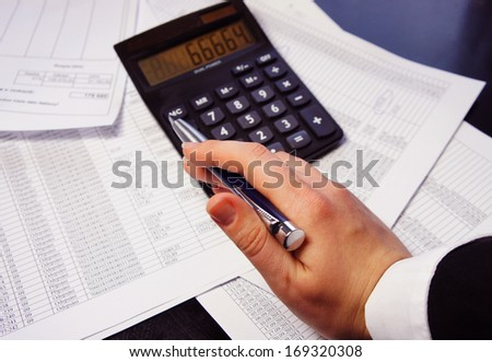 Calculator, pen and accounting document with a lot of numbers