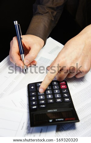 Calculator, pen and accounting document with a lot of numbers and man hands