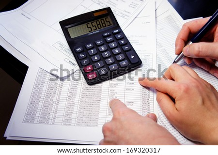 Calculator, pen and accounting document with a lot of numbers and woman hands