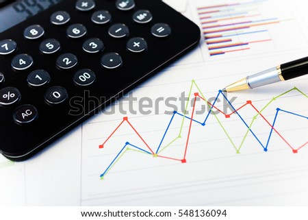 Calculator, pen and financial charts