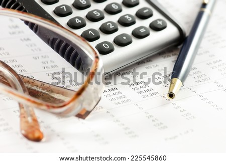 Calculator pen and pair of glasses on a financial report.