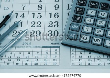 Calculator, pen and pencils on calendar background - stock photo