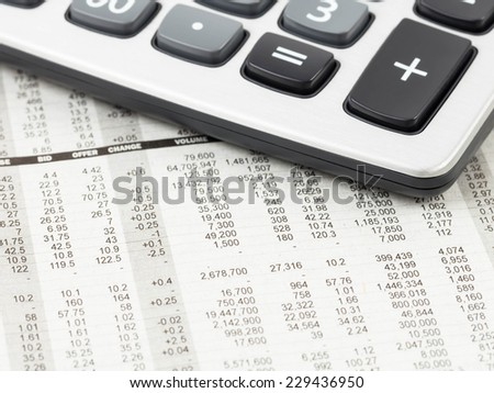 Calculator rest on stock price detail financial newspaper - stock photo