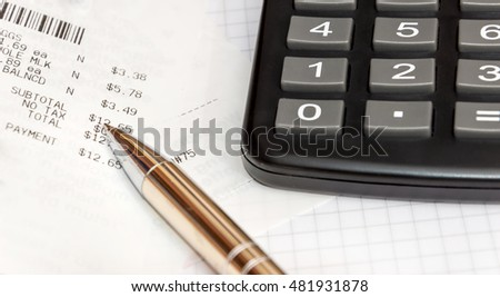 calculator, store's bills and pen on the notepad