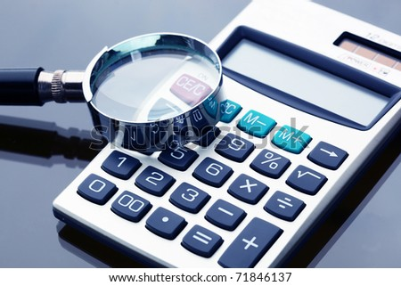 Calculator  with a magnifying glass on a white background