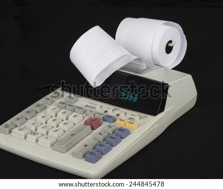 Calculator with adding paper on a black surface/Calculator/Product photograph of a calculator on black surface - stock photo