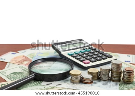 Calculator with coin and Magnifying glass on money banknotes Euro and Dollars,concept of business planning and finance and savings - stock photo