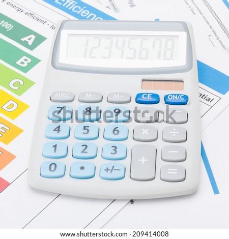 Calculator with energy efficiency chart - studio shot - 1 to 1 ratio - stock photo