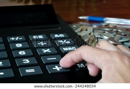 Calculator with hand , pluss make money - stock photo