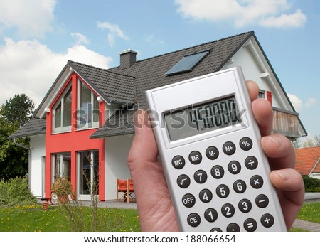 Calculator with high sum in the display in front of a house - stock photo