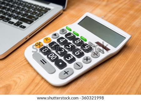 Calculator with laptop on wooden background