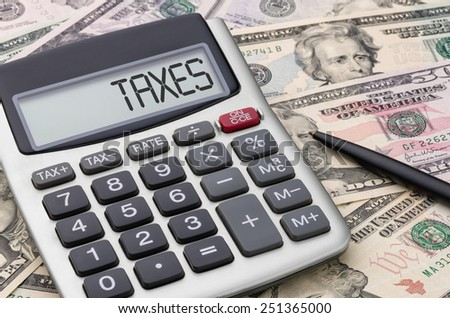 Calculator with money - Taxes - stock photo