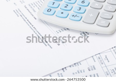 Calculator with monthly utility bill under it - stock photo