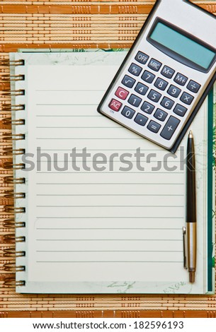 Calculator with notebook & pen on bamboo wooden background