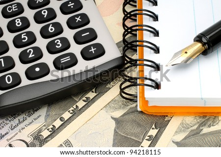 Calculator with notepad and pen on money background - stock photo