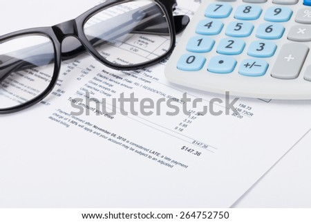 Calculator with pen, glasses and utility bill under it - stock photo