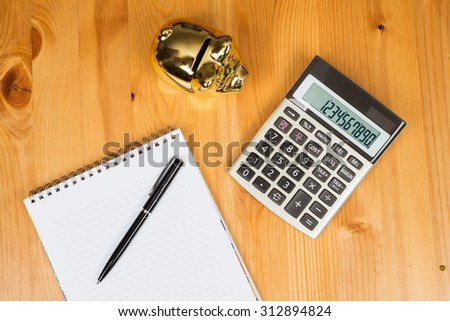 Calculator With Piggybank and a notepad - stock photo