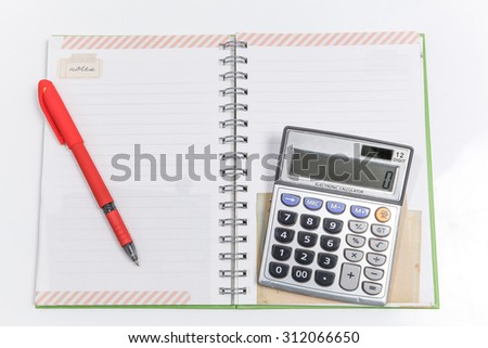 calculator with red pen on a blank white notebook