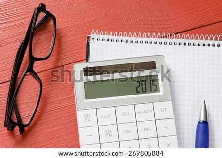 Calculator with 2015 sign. Calculator with 2015 sign, notepad, pen and glasses - stock photo