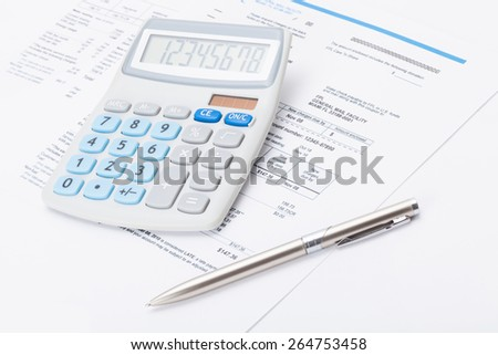 Calculator with silver pen and utility bill under it - stock photo