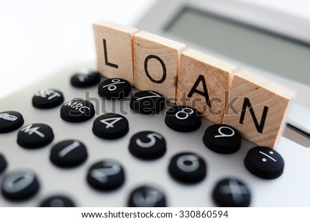 Calculator with the word loan written in wooden block letters - stock photo
