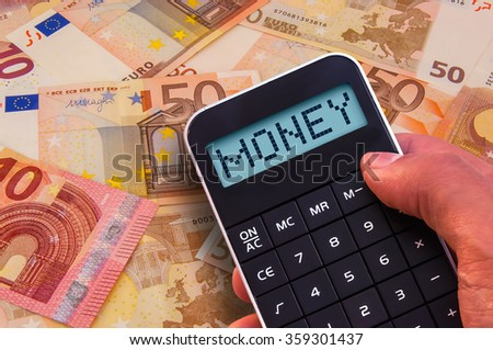 Calculator with the word Money on the display and banknotes background
