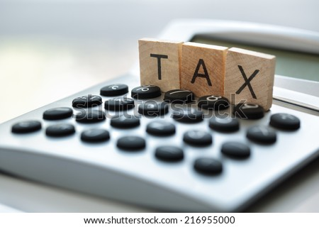 Calculator with the word tax written in wooden block letters - stock photo