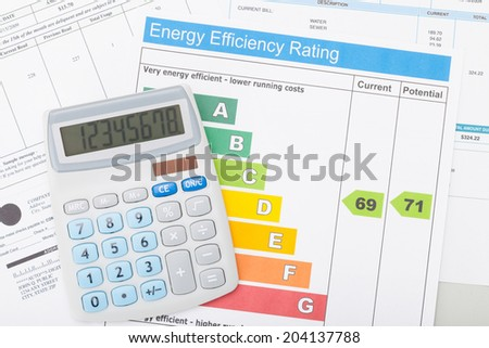 Calculator with utility bill and energy efficiency chart - stock photo