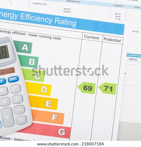Calculator with utility bill and energy efficiency chart - 1 to 1 ratio - stock photo