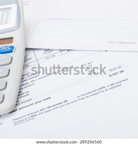 Calculator with utility bill under it - close up studio shot