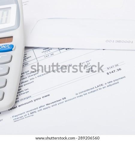 Calculator with utility bill under it - close up studio shot - stock photo