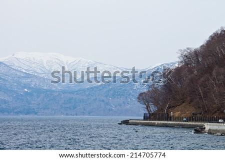 caldera lake in early spring,Lake Shikotsuko, Hokkaido, Japan - stock photo