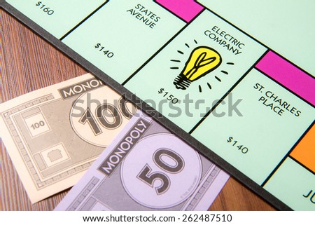 CALDWELL, IDAHO/USA - MARCH 16, 2015: 150 being paid to the Electric company in Monopoly - stock photo