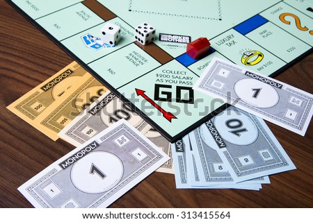 CALDWELL, IDAHO/USA - MARCH 16, 2015: Game of monopoly with cash thrown about near the collect go section - stock photo