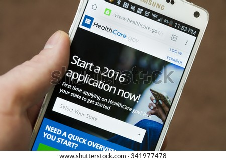 CALDWELL, IDAHO/USA NOVEMBER 18, 2015: On a mobile device a man looks up how to apply for healthcare in Caldwell, Idaho - stock photo