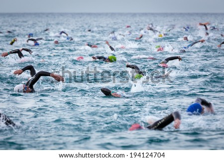 CALELLA, SPAIN -Â?Â? MAY 18:  Triathletes on start of the Ironman triathlon competition at Calella beach, May 18, 2014 in Calella, Spain  - stock photo