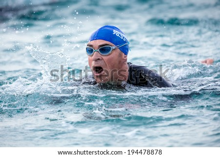 CALELLA, SPAINÂ?Â? MAY 18:  Triathletes swim on start of the Ironman triathlon competition at Calella beach, May 18, 2014 in Calella, Spain - stock photo
