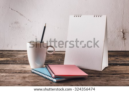 Calendar , cup ,pencil and book on wooden floor