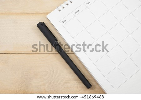 calendar date and pen on wooden background - stock photo