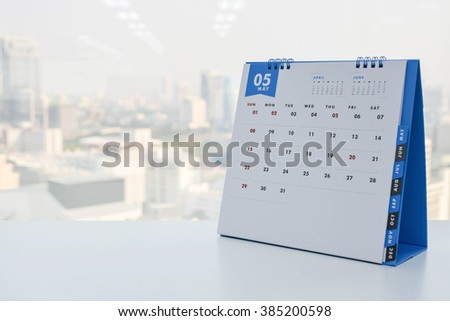 Calendar of May on the white table with city view background - stock photo