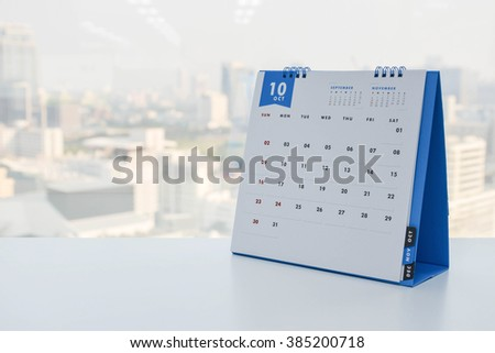 Calendar of October on the white table with city view background - stock photo