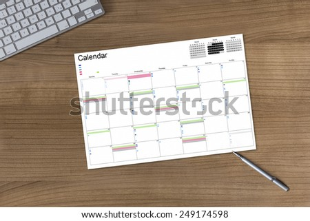 Calendar on a wooden table with modern keyboard and silver pen - stock photo