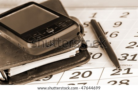 Calendar page, pen, pocket planner and PDA - stock photo