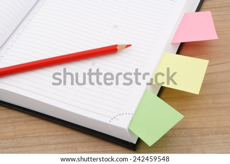 calendar page with red pencil and multi colored post it on wooden table - stock photo
