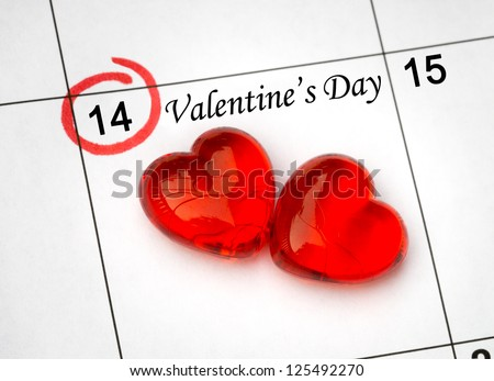 Calendar page with the red hearts on February 14 of Saint Valentines day. - stock photo