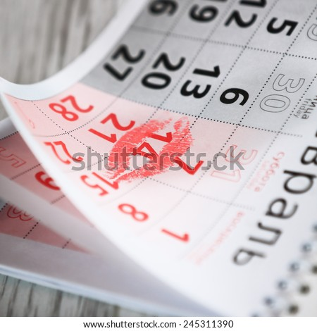 Calendar page with the red kiss on February 14 of Saint Valentines day. - stock photo