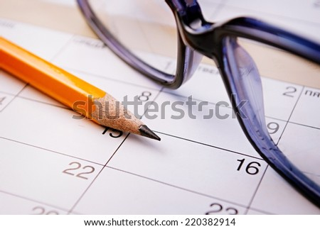 Calendar, pencil and glasses for planning important things and to set a date. - stock photo