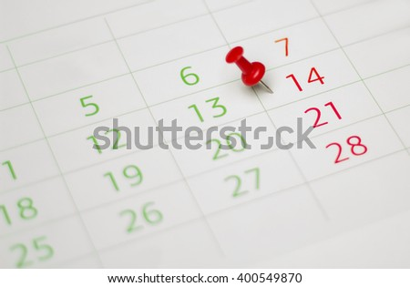 Calendar with red push pin. Shallow depth of field.